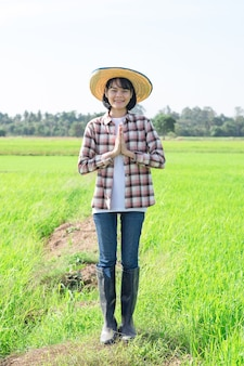 立ち上がって、稲作農家で敬意を表して胸や額に手を押し付けるアジアの農家の女性