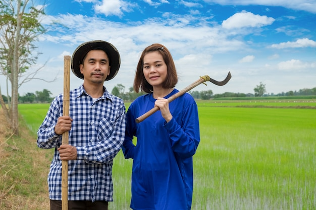 Asian farmers couple holding tools in rice farm at thailand