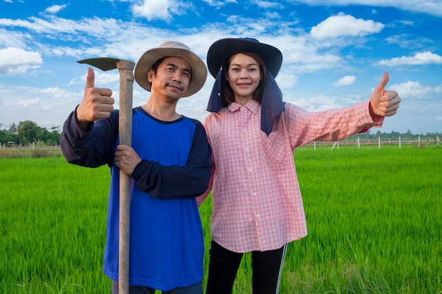 Asian farmers couple holding tools and thumb up in rice farm