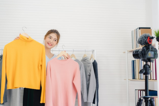 Asian fashion female blogger online influencer holding shopping bags and lots of clothes
