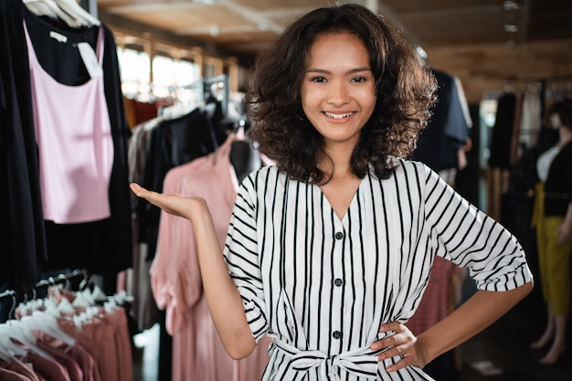 Asian fashion shop owner presenting her shop