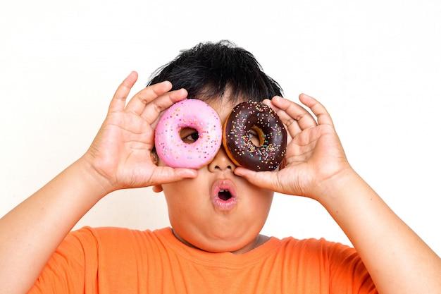アジアの太った少年は、チョコレートコーティングとイチゴコーティングの2つのドーナツを持っています。彼は食べることを楽しんでいます。子供の身体的な健康問題を引き起こす食品の概念は、病気を引き起こします。