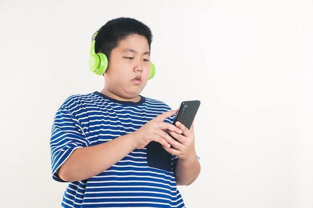 スマートフォンを再生して立っているアジアの太った少年ヘッドフォンを着用