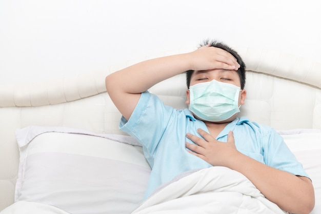 Asian fat boy wear surgical mask with a high fever and chest pain on bed,