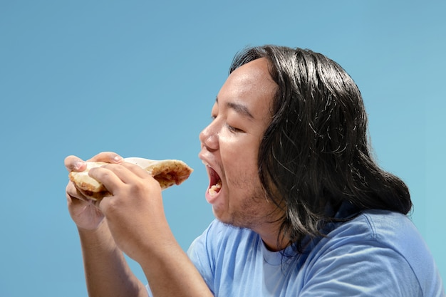 Asian fat man eating slice of pizza fast food