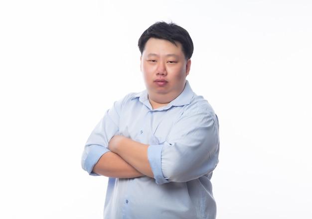 Азиатский толстый человек в руках синей рубашке пересек и смотрит в камеру, изолированные на белой стене