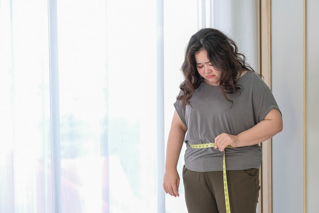 Asian fat woman is sad because of the increase in size after checking with a tape measure.