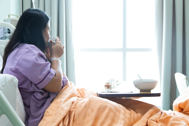 新しい医療センターのベッドに横たわって幸せを感じているアジアの太った女性患者。ベッドと快適な医療を備えた回復室