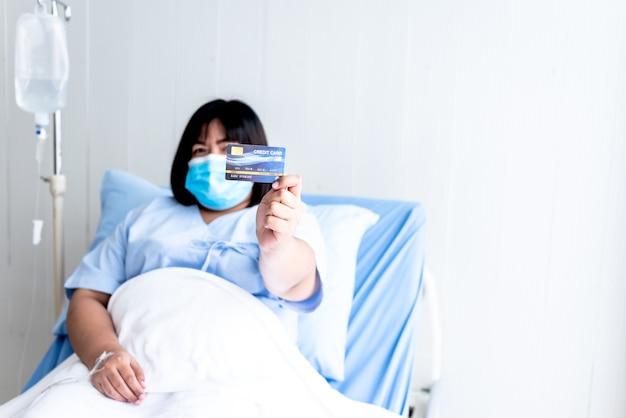 患者のベッドに座っているマスクを身に着けているアジアの太った女性患者モックアップクレジットカードを表示