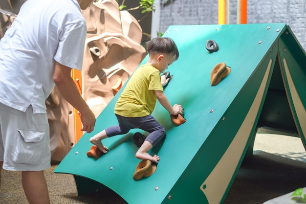 Asian father and 2 - 3 years old toddler child having fun trying to climb on artificial boulders at playground, little boy climbing up a rock wall