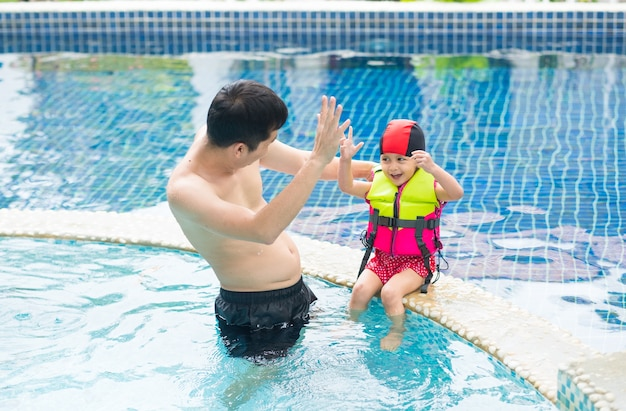 Asian father and adorable daughter are talking and smiling in the pool