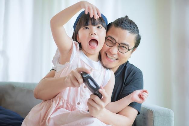아시아 아버지와 귀여운 딸이 집에서 휴가를 즐기고 콘솔 게임을 즐기십시오.