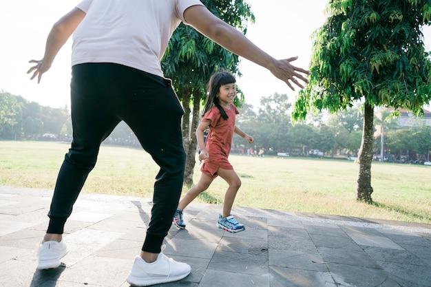 Азиатские отец и дочь делают упражнения, ловят и играют вместе