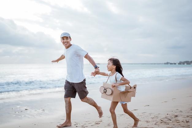 ビーチで走っているアジアの父と娘は、段ボールのおもちゃの飛行機で遊ぶ