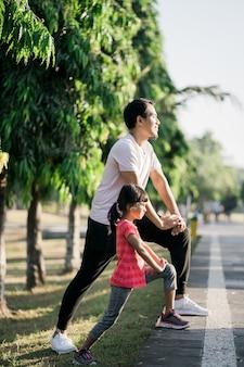 Азиатские отец и дочь растяжения и спорта на открытом воздухе