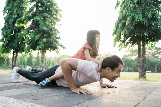 Азиатский отец и маленькая дочь делают упражнения на открытом воздухе здорового образа жизни семьи с ребенком
