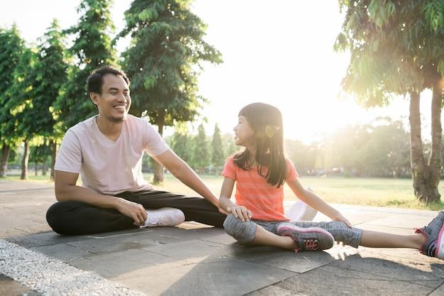 Азиатский отец и маленькая дочь делают упражнения на открытом воздухе