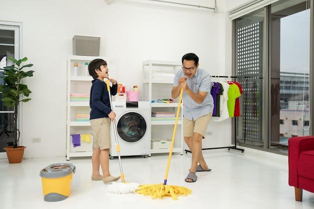 Азиатские отец и сын делают уборку в доме. молодой человек и девочка вытирают пыль, моют пол полотенцем и спреем в гостиной.