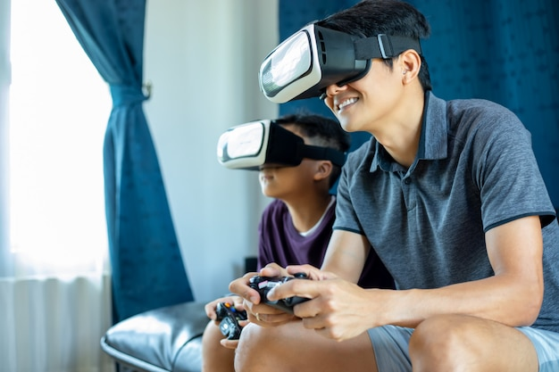 アジアの父と息子は、ビデオジョイスティックやバーチャルリアリティグラスと一緒にビデオゲームを楽しみ、自宅のリビングルームでエキサイティングでとても楽しい