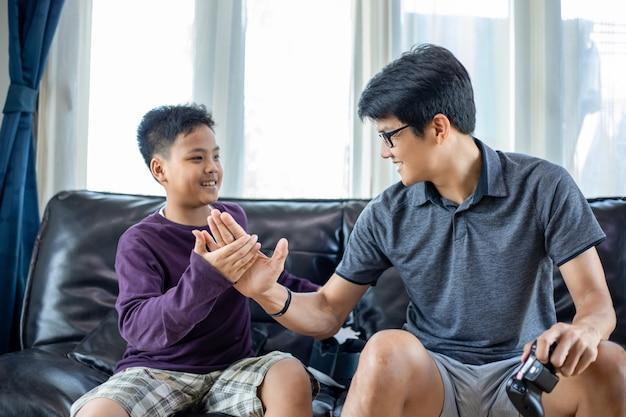 アジアの父と息子は、自宅のリビングルームで興奮して非常に楽しいビデオジョイスティックと一緒にビデオゲームを楽しむ