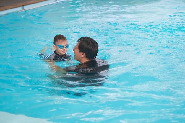 アジアの父と息子は屋内スイミングプールで水泳のレッスンを受けます、かわいい小さなアジアの3歳の幼児の男の子は、彼のお父さんと一緒に泳ぐことを学ぶ水泳ゴーグルを身に着けています