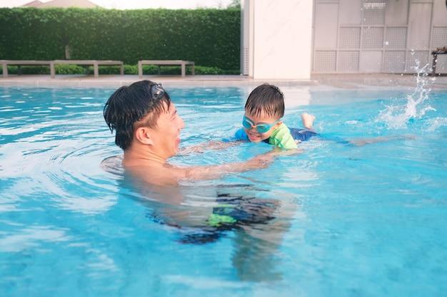 아시아 아버지와 아들이 수영장에서 수영 레슨을 걸립니다