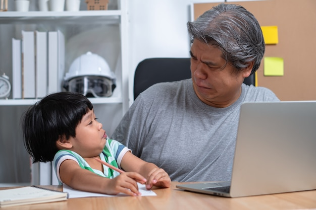 Asian father attempt to work at the home office with a laptop with a daughter who came into chaos