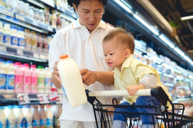 Asian father &  boy child choosing milk product in grocery store