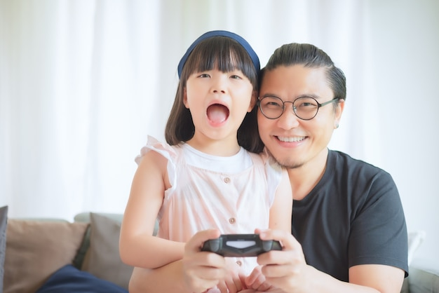 Asian father and cute daughter enjoy and play console game on vacation at home