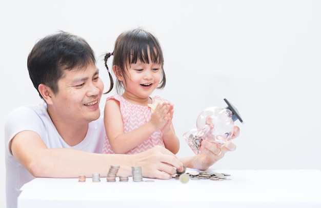 Asian father and daughter are insert the coins to piggy bank.