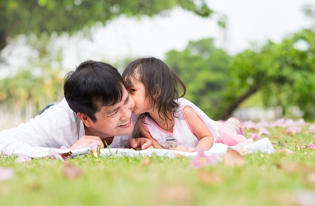 Asian father and daughter are lying and kissing together on the green lawn.