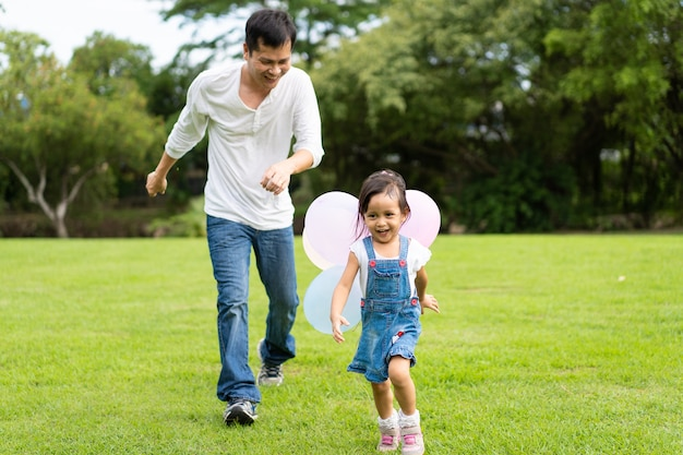 Asian father and daughter are playing the balloons and running together in the park
