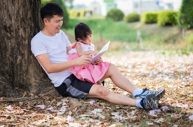 Asian father and daughter are reading the book together in the park
