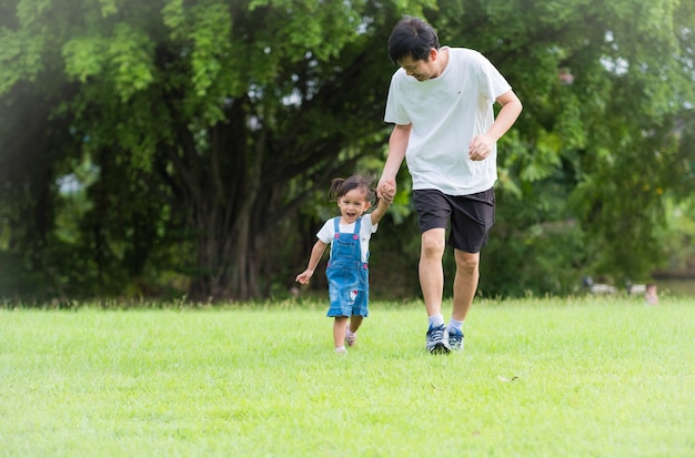 Asian father and daughter are running together on the green field