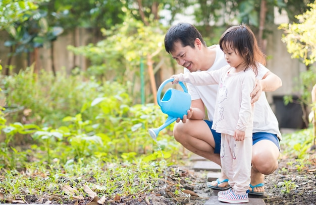 Asian father and daughter are watering vegetables garden at home.