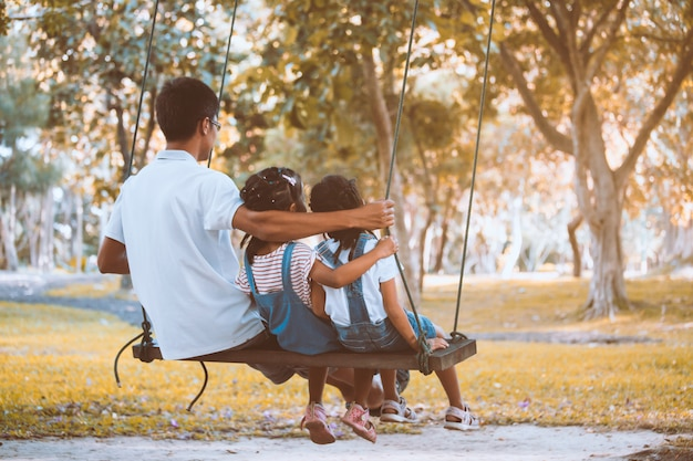Asian father and daughter having fun to ride on swings together in playground at the park