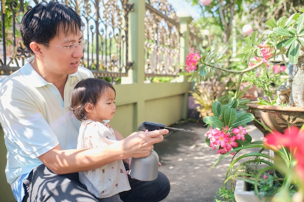 Asian father and daughter having fun using spray bottle watering plants at home in sunny morning