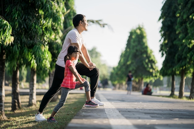 Asian father and daughter stretching and sport outdoor
