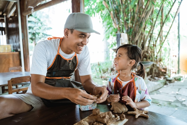 Asian father and daughter working with clay