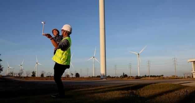 풍력 터빈 농장에서 아들을 안고 즐기는 아시아 아버지 엔지니어