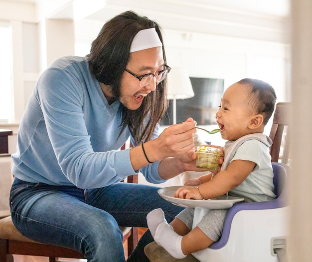 赤ちゃんの息子にピューレを与えるアジア人の父親