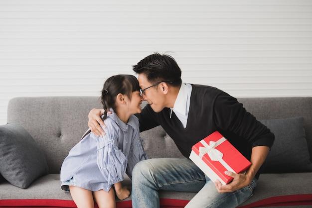アジアの父親は娘へのプレゼントを差し出しキスをします。誕生日のためのコンセプトサプライズギフトボックス。
