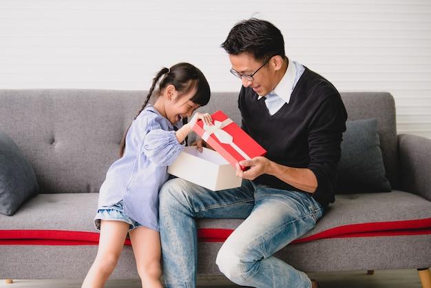 アジアの父親は娘へのプレゼントを差し出します。誕生日のためのコンセプトサプライズギフトボックス。