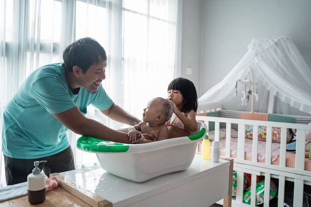 Asian father giving bath to his baby toddler