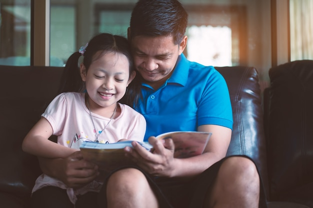 Asian father and his daughter reading a book at home