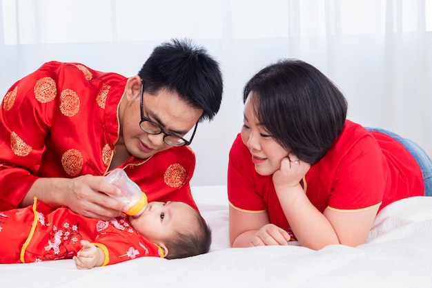 Asian father hold bottle milk for son toddler bed at home while mother look at baby with love, new family red chinese costume nursing feeding infant, lifestyle family in chinese new year festival