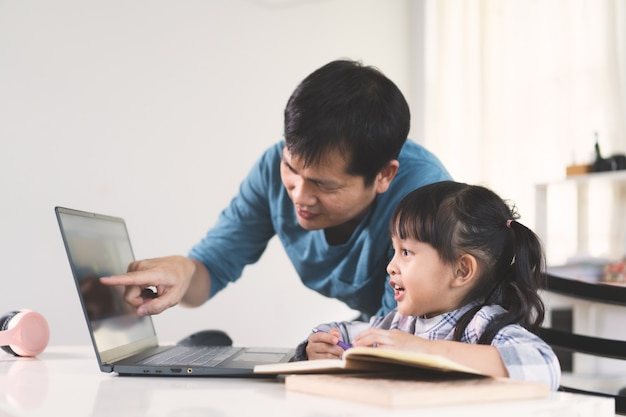 Asian father is helping and support daughter to studying the lesson of online class.