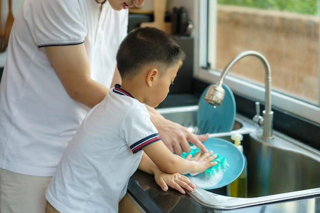 Asian father is teaching his son how to wash dishes, help with housework in the kitchen at home, fathers interact with their children throughout the day.