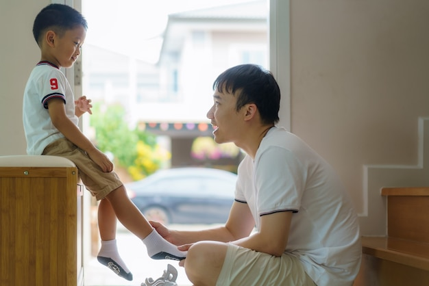 Asian father is wearing socks for his son, fathers interact with their children throughout the day.