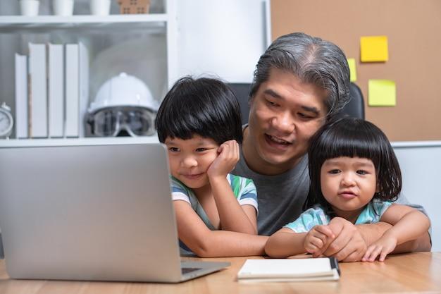 アジアの父親は娘と一緒に家で仕事をしていて、学校でのオンライン学習を一緒に勉強しています。